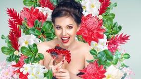 Vrouw met glas vruchten en bessen voor bloemenachtergrond royalty-vrije stock fotografie