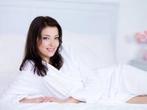 Vrouw met glimlach op een bed Royalty-vrije Stock Afbeelding