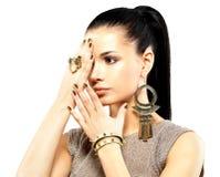 Vrouw met gouden spijkers en mooie gouden juwelen stock foto's