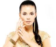Vrouw met gouden spijkers en mooie gouden juwelen Stock Afbeelding