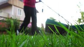 Vrouw met grasmaaier in de binnenplaats stock videobeelden