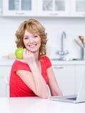 Vrouw met groene appel in de keuken Stock Foto