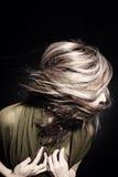 Vrouw met haar dat in wind fladdert Stock Foto's