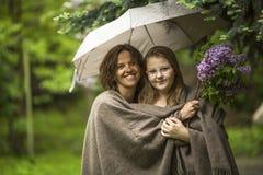 Vrouw met haar dochter die zich in het Park onder een paraplu bevinden Liefde Royalty-vrije Stock Afbeelding