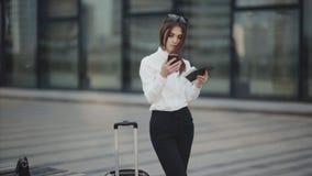 Vrouw met haar online registratie van de zoonscontrole op haar mobiele telefoon in luchthavenzaal stock videobeelden