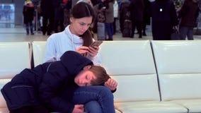 Vrouw met haar vermoeide zoon bij de luchthavenzaal met een mobiele telefoon in haar handen die op vlucht wachten stock videobeelden
