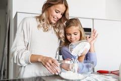 Vrouw met haar weinig zuster binnen thuis keuken het koken met bloem royalty-vrije stock afbeeldingen