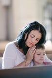 Vrouw met haar zoon het bidden Stock Foto's
