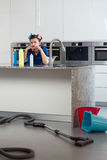 Vrouw met haarrollen het zitten bored in een mooie keuken royalty-vrije stock foto's