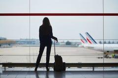 Vrouw met handbagage in internationale luchthaven, die door het venster vliegtuigen bekijken stock afbeeldingen