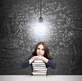 Vrouw met handen en hoofd op stapel van boeken het denken stock afbeeldingen