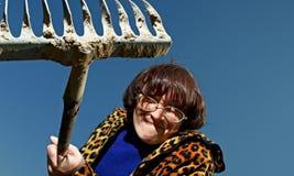 Vrouw met hark Stock Foto