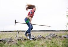 Vrouw met hark tussen benen in hop Stock Foto