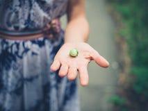 Vrouw met hazelnoot in haar hand royalty-vrije stock afbeeldingen