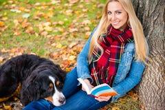Vrouw met het boek van de hondlezing in de herfstpark Stock Afbeeldingen