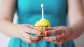 Vrouw met het branden van kaars op verjaardag cupcake stock footage
