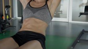 Vrouw met het doordringen op haar maagpompen een pers in geschiktheidsclub stock video