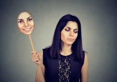 Vrouw met het droevige uitdrukking nemen van een masker die opgewektheid uitdrukken stock afbeelding