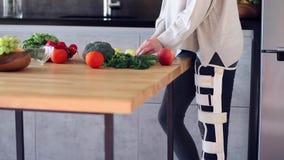Vrouw met het gebroken been koken in keuken stock videobeelden