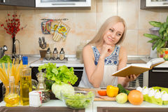 Vrouw met het koken boekzitting bij de keukenlijst Stock Afbeeldingen