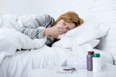 vrouw met het niezen neus die in weefsel op bed blazen die aan de koude symptomen lijden die van het griepvirus geneesmiddelen ta Stock Foto's