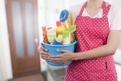 Vrouw met het schoonmaken van materiaal klaar om huis schoon te maken Royalty-vrije Stock Foto