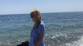 Vrouw met het sluiten van parasolgangen op kust stock footage