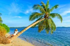 Vrouw met het traditionele Aziatische hoed ontspannen op tropische strandzitting op kokosnotenpalm in de zonnestraal echte mensen royalty-vrije stock afbeelding