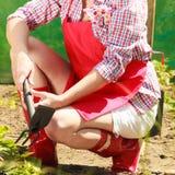 Vrouw met het tuinieren hulpmiddel die in tuin werken Royalty-vrije Stock Afbeelding