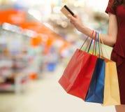 Vrouw met het winkelen zakken en creditcard bij opslag Royalty-vrije Stock Afbeeldingen