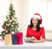 Vrouw met het winkelen zakken en de computer van tabletpc Royalty-vrije Stock Afbeeldingen