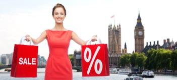 Vrouw met het winkelen zakken over de stad van Londen Stock Afbeeldingen
