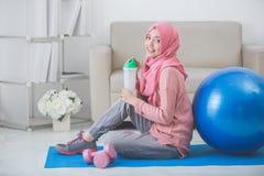 Vrouw met hijab die oefening thuis doen stock afbeeldingen