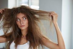 Vrouw met Holdings Lang Beschadigd Droog Haar Haarschade, Haircare stock afbeelding