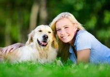 Vrouw met hond die op het gras liggen stock afbeelding