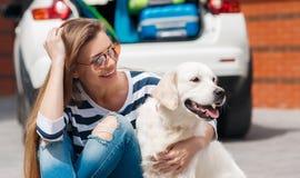 Vrouw met hond door autohoogtepunt van koffers Stock Afbeelding