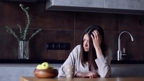 Vrouw met hoofdpijnzitting in keuken stock video