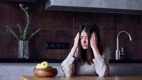 Vrouw met hoofdpijnzitting in keuken stock footage