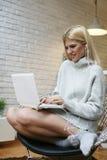 Vrouw met hoofdtelefoons die aan muziek luisteren en laptop met behulp van Stock Afbeelding