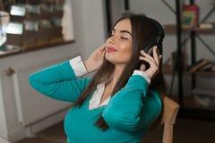 Vrouw met hoofdtelefoons op stoel royalty-vrije stock afbeelding