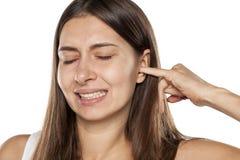 Vrouw met jeukerig oor stock afbeeldingen