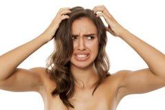 Vrouw met jeukerige scalp royalty-vrije stock afbeelding