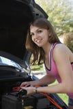 Vrouw met Jumper Cables By Car Stock Afbeeldingen