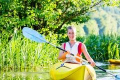 Vrouw met kajak of kano op rivier Stock Foto
