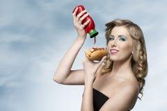 Vrouw met ketchup en hotdog Stock Afbeelding
