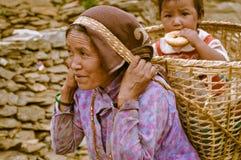 Vrouw met kind in mand in Nepal Stock Afbeelding