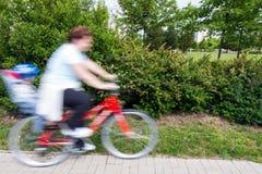 Vrouw met kind op fiets stock afbeeldingen