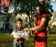 Vrouw met kinderen in tuin hangende wasserij Royalty-vrije Stock Foto's