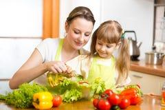 Vrouw met kindkok bij keuken royalty-vrije stock afbeelding