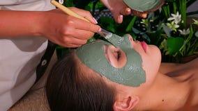 Vrouw met klei gezichtsmasker in beauty spa